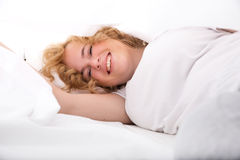 Junge Frau, die im Bett unter den Blättern sich versteckt Lizenzfreies Stockbild