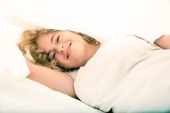 Junge Frau, die im Bett unter den Blättern sich versteckt Lizenzfreie Stockfotografie