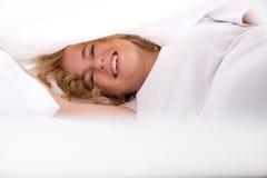 Junge Frau, die im Bett unter den Blättern sich versteckt Stockfotografie