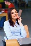 Junge Frau, die im Büro sitzt Stockfoto