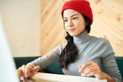Junge Frau, die im Café Blogging ist Lizenzfreie Stockbilder