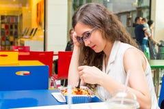 Junge Frau, die im Café isst Stockfoto