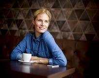 Junge Frau, die im Café sitzt Lizenzfreies Stockfoto