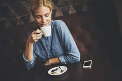 Junge Frau, die im Café sitzt Lizenzfreies Stockbild