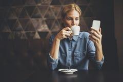 Junge Frau, die im Café sitzt Stockfotos