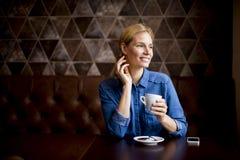 Junge Frau, die im Café sitzt Stockfoto
