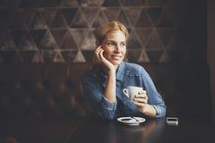 Junge Frau, die im Café sitzt Stockbild