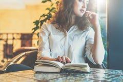 Junge Frau, die im Café am Tisch mit einem Papierbuch sitzt Mädchenwartefreunde im Restaurant- und Lesebuch Stockfotos