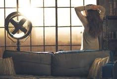 Junge Frau, die im Fenster in der Dachbodenwohnung schaut stockfoto