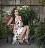 Junge Frau, die im geflochtenen Stuhl auf Patio im Freien sitzt lizenzfreie stockbilder