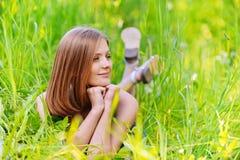 Junge Frau, die im Gras liegt Stockfotografie