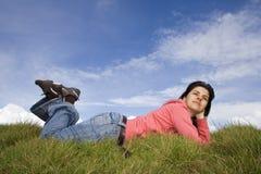Junge Frau, die im Gras liegt Lizenzfreie Stockbilder