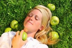 Junge Frau, die im Gras liegt Stockbild