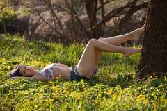 Junge Frau, die im Gras liegt Lizenzfreie Stockfotografie