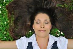 Junge Frau, die im Gras mit Blumen liegt Stockbild