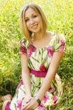Junge Frau, die im Gras sich entspannt Stockbilder