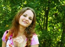 Junge Frau, die im Gras sich entspannt Stockfotografie