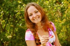Junge Frau, die im Gras sich entspannt Lizenzfreies Stockbild