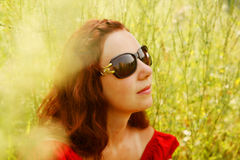 Junge Frau, die im Gras sich entspannt Lizenzfreies Stockfoto