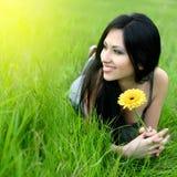 Junge Frau, die im Gras sich entspannt Stockfoto