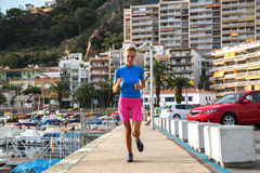 Junge Frau, die im Hafen im bunten sportwear rüttelt Lizenzfreies Stockfoto
