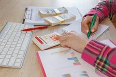 Junge Frau, die im Haus, sitzend am Schreibtisch, unter Verwendung des Computers arbeitet Geschäftsbewilligung und Finanzkonzept lizenzfreie stockfotografie