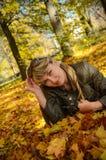 Junge Frau, die im hellen Herbstpark sich entspannt Stockfoto