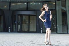 Junge Frau, die im Hintergrund des Geschäftszentrums steht Stockfotos