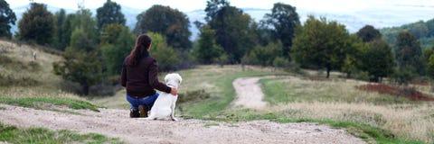 Junge Frau, die im Horizont mit Welpen schaut Stockbild