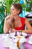 Junge Frau, die im Kaffee stillsteht Stockfoto