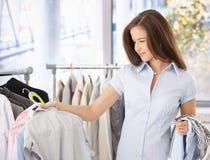 Junge Frau, die im Kleidungspeicher schaut lizenzfreies stockfoto