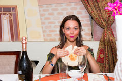 Junge Frau, die im marokkanischen Restaurant sitzt und Pittabrot brea hält stockfoto