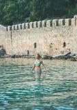 Junge Frau, die im Meer am Strand nahe Festungswand steht Lizenzfreie Stockbilder