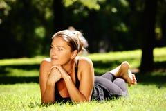 Junge Frau, die im Park liegt Stockfoto
