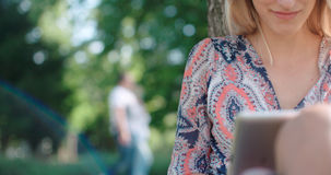 Junge Frau, die im Park sitzt und digitale Tablette verwendet Lizenzfreie Stockfotos