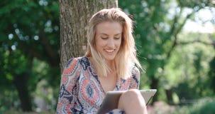 Junge Frau, die im Park sitzt und digitale Tablette verwendet Stockbild