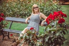 Junge Frau, die im Park stillsteht Stockfotos
