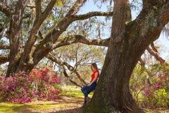 Junge Frau, die im Park unter Eiche mit spanischem Moos sich entspannt lizenzfreie stockfotografie