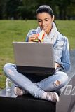Junge Frau, die im Park unter Verwendung des Laptops zu Mittag isst Stockbild