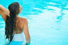 Junge Frau, die im Pool sich entspannt. Hintere Ansicht Stockbilder
