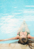 Junge Frau, die im Pool sich entspannt. hintere Ansicht Lizenzfreies Stockfoto