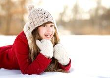 Junge Frau, die im Schnee liegt Stockfotografie