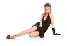 Junge Frau, die im schwarzen Kleid sitzt Stockfoto