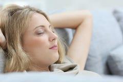 Junge Frau, die im Sofa sich entspannt Lizenzfreie Stockfotografie