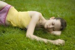 Junge Frau, die im Sommerpark liegt lizenzfreie stockfotos