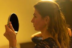 Junge Frau, die im Spiegel schaut lizenzfreie stockfotografie