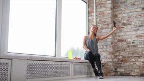 Junge Frau, die im Sport sich engagierte, macht Fotos von an einem Handy stock footage
