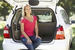 Junge Frau, die im Stamm des Autos sitzt Stockfoto