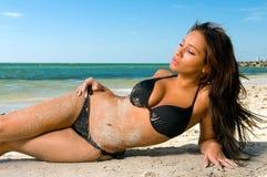 Junge Frau, die im Strand ein Sonnenbad nimmt Lizenzfreies Stockfoto