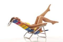 Junge Frau, die im Strandstuhl sich entspannt Stockbilder